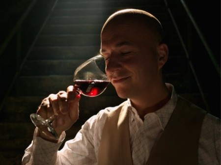Man tasting wine, smiling, eyes closed
